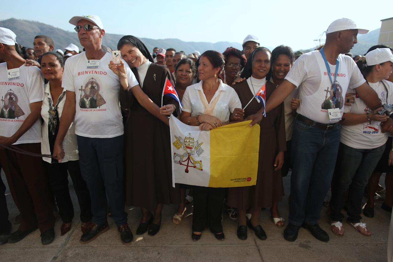 Faithful wait for Pope Benedict XVI at the church of the Virgin of Charity of Cobre, Cuba's patron saint, in Santiago de Cuba, Cuba Tuesday March 27, 2012. Benedict XVI is in the second day of his Cuban tour. (AP Photo/Esteban Felix, Pool)