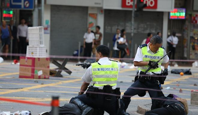 An armed police officer, who just fired three live rounds, tries to stop two protesters from blocking a road in Sai Wan Ho on Monday morning. Photo: Nova Tam