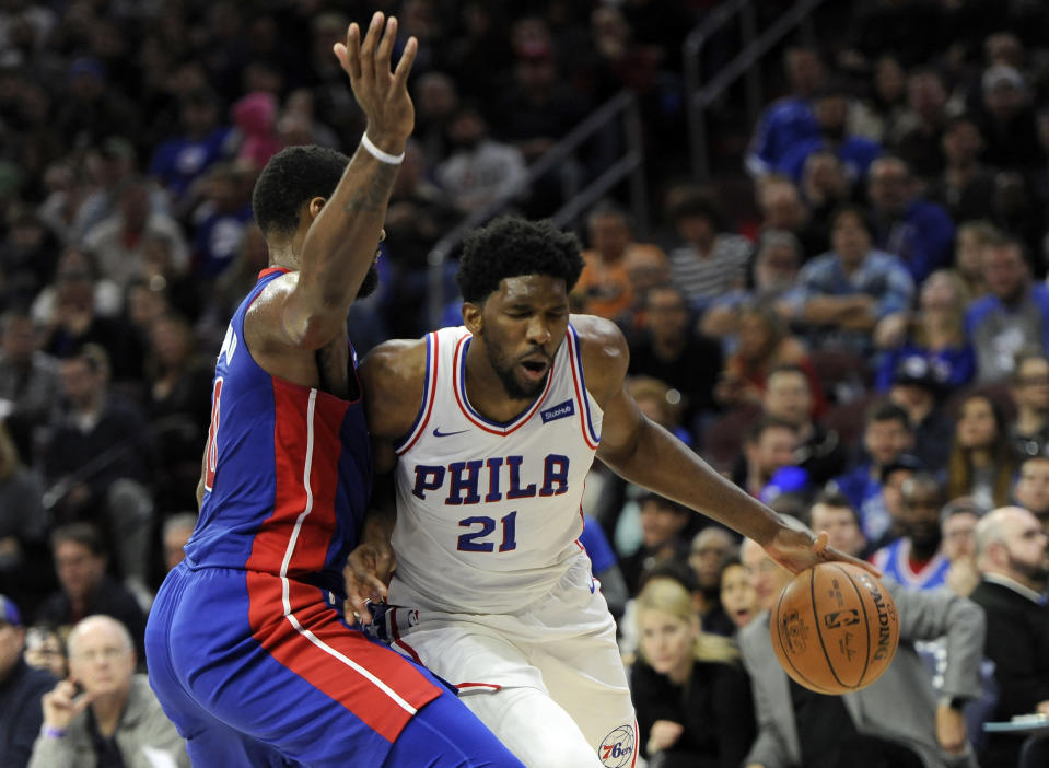 Joel Embiid (21) drives to the basket past Andre Drummond. (AP)