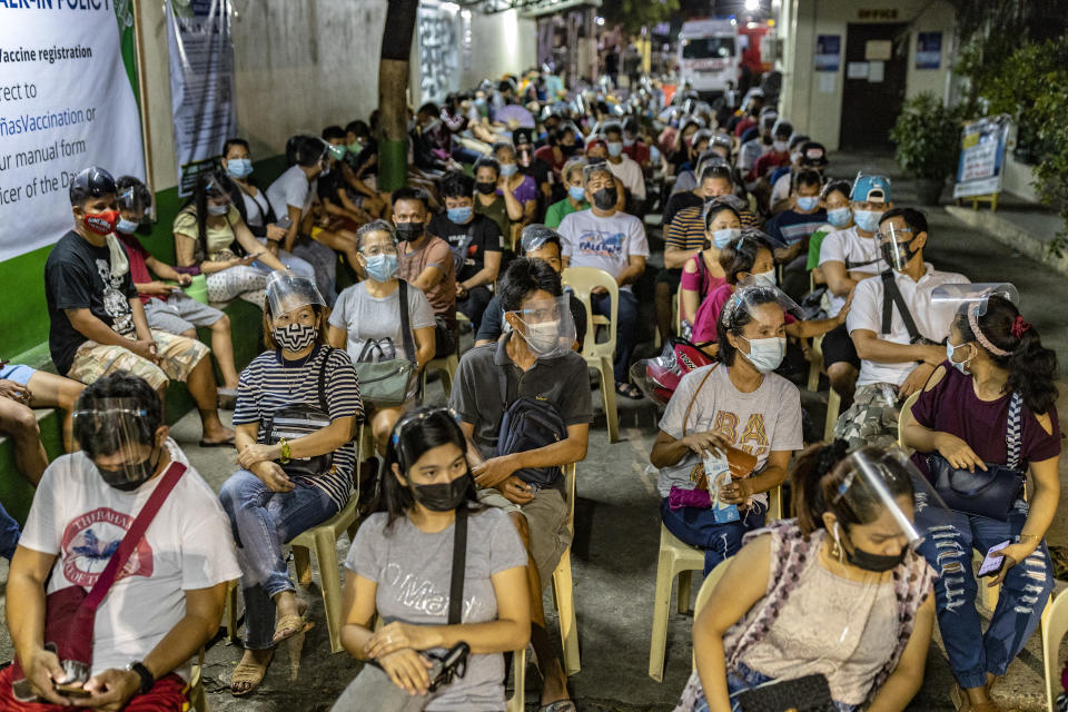 People hoping to get vaccinated against COVID-19 sit while queuing outside a vaccination site on August 08, 2021 in Las Pinas, Metro Manila, Philippines. (Photo: Ezra Acayan/Getty Images)