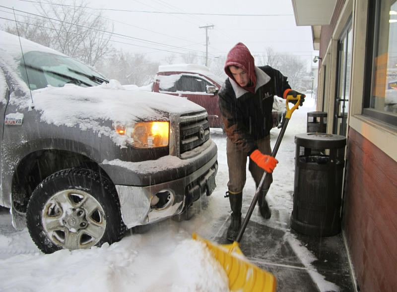 Carter Martin shovels a sidewalk at Maplefields store and gas station on Sunday, Jan. 20, 2019, in Plainfield, Vt. A major winter storm that blanketed most of the Midwest with snow earlier in the weekend barreled toward New England Sunday, where it was expected to cause transportation havoc ranging from slick and clogged roads to hundreds of cancelled airline flights. (AP Photo/Lisa Rathke)