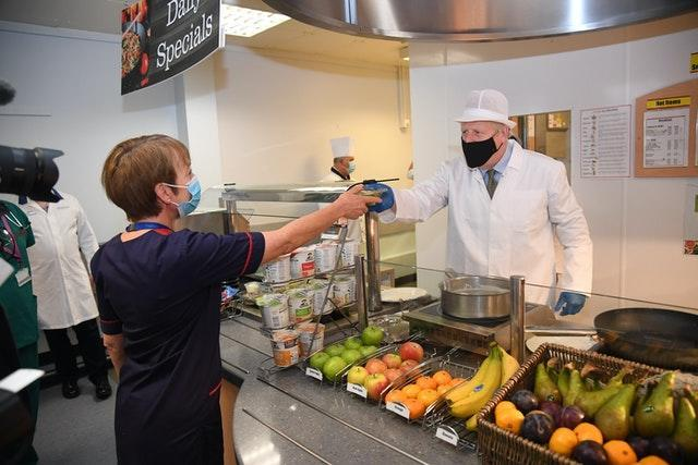 Prime Minister Boris Johnson serving up a meal during a visit to Royal Berkshire Hospital, Reading