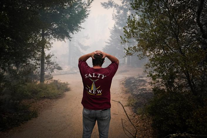 Peter Koleckar is overwhelmed by the sight of multiple homes burned in his neighborhood after the CZU August Lightning Complex Fire passed through Aug. 20 in Bonny Doon, Calif.
