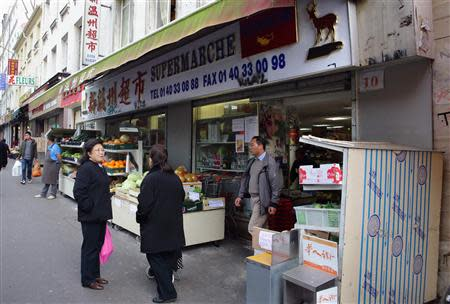 People stand outside a supermarket bearing a Chinese signboard in the Belleville district in Paris