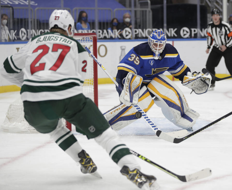 St. Louis Blues goaltender Ville Husso (35) stops a point blank shot from Minnesota Wild's Nick Bjugstad (27) in the first period of an NHL hockey game, Wednesday, May 12, 2021 in St. Louis. (AP Photo/Tom Gannam)