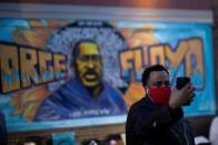 A local resident takes a selfie in front of a mural of George Floyd after the verdict in the trial of former Minneapolis police officer Derek Chauvin, found guilty of the death of George Floyd, at George Floyd Square in Minneapolis, Minnesota, U.S.