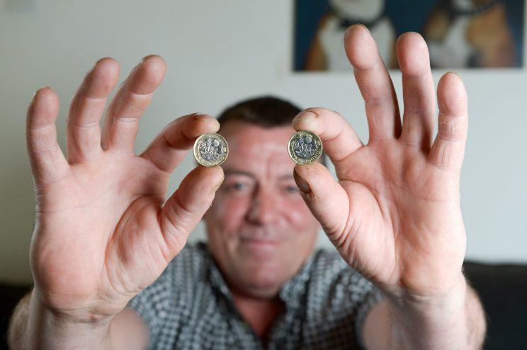Roy Wright shows off what he believes to be a fake new £1 coin (SWNS)