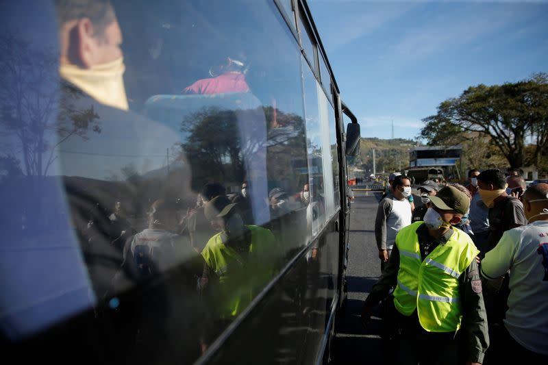 A member of the Bolivarian National Guard checks if people onboard a bus are wearing their protective masks before allowing them to pass through a checkpoint into Caracas