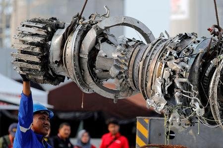 FILE PHOTO: A worker assists his colleague during the lifting of a turbine engine of the Lion Air flight JT610 jet, at Tanjung Priok port in Jakarta