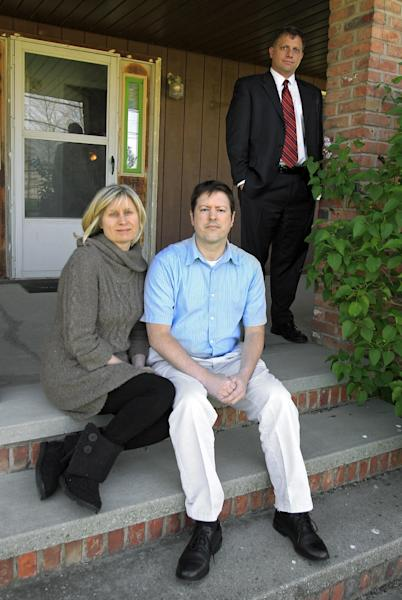 In this Tuesday, April 24, 2012 photo, Sarah and Devin Stang sit on the porch of the home they are renting in LaGrange, Ohio. Their bankruptcy attorney Matthew H. Barrett stands at right. The Stangs filed for bankruptcy and lost their Sandusky, Ohio home to foreclosure, but due to a 2005 law their student loan debts are still not dischargeable. (AP Photo/Mark Duncan)