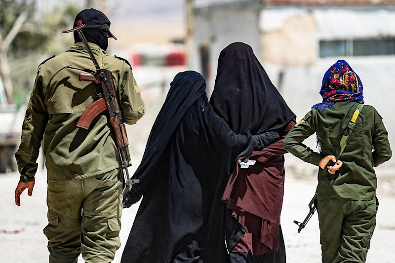 An internal security patrol escorts women, reportedly wives of Islamic State (IS) group fighters, in the al-Hol camp in al-Hasakeh governorate in northeastern Syria: AFP