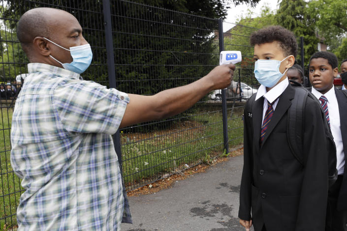 Year seven pupils have their temperature taken by member of support staff Adelaja Balogun, as they arrive for their first day at Kingsdale Foundation School in London, Thursday, Sept. 3, 2020. (Kirsty Wigglesworth/AP Photo)