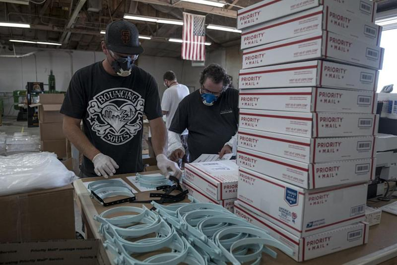 Workers pack orders for face shields at Mask & Shield, a division of Monster City Studios, in Fresno, California, in May.