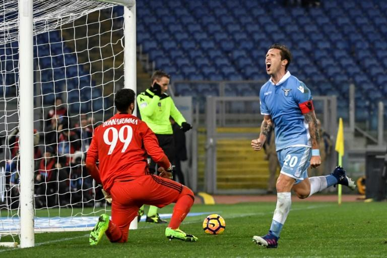 Lazio's midfielder from Argentina Lucas Biglia (R) celebrates after scoring a penalty next to AC Milan's goalkeeper from Italy Gianluigi Donnarumma (L) during the Italian Serie A football match Lazio vs Milan on February 13, 2017