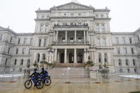 Michigan State Police officers patrol outside the state Capitol in Lansing, Mich., Friday, Jan. 15, 2021. With the FBI warning of potential violence at all state capitols Sunday, Jan. 17, the ornate halls of government and symbols of democracy looked more like heavily guarded U.S. embassies in war-torn countries. (AP Photo/Carlos Osorio)
