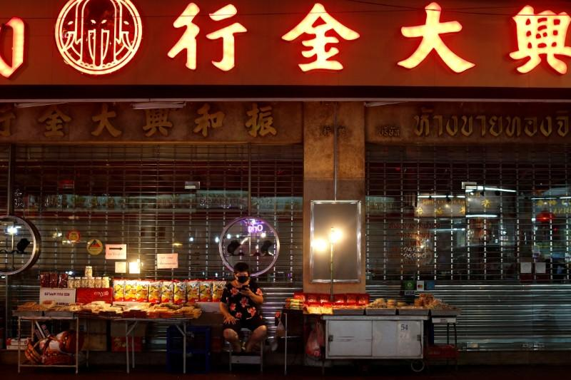 A woman wearing a mask waits for customers at an empty food stall during the coronavirus disease (COVID-19) outbreak, in Chinatown, Bangkok