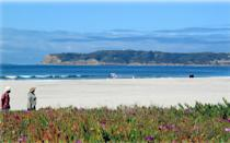 """<p><strong>Let's start big picture. What's the vibe here?</strong><br> Deserving of its spot on the list of best beaches in America, Coronado is praised for its sparkling, pillow-soft sand; ample clean, sandy beach; and Zen vacation getaway vibes. Driving over the Coronado Bridge feels as if you're leaving San Diego and traveling to an entirely new locale.</p> <p><strong>Any standout features or must-sees?</strong><br> Head to the storied <a href=""""https://www.cntraveler.com/hotels/united-states/coronado/hotel-del-coronado?mbid=synd_yahoo_rss"""" rel=""""nofollow noopener"""" target=""""_blank"""" data-ylk=""""slk:Hotel del Coronado"""" class=""""link rapid-noclick-resp"""">Hotel del Coronado</a> for a sustainable seafood dinner at <a href=""""https://www.cntraveler.com/restaurants/coronado/serea-coastal-cuisine?mbid=synd_yahoo_rss"""" rel=""""nofollow noopener"""" target=""""_blank"""" data-ylk=""""slk:Serẽa"""" class=""""link rapid-noclick-resp"""">Serẽa</a> or happy hour at Sun Deck Grill, and keep an eye out during low tide to see a sunken ship peak out of the water. At the north end of the island, Coronado's Dog Beach is a favorite with those who wish to let their pup run off-leash.</p> <p><strong>Was it easy to get around?</strong><br> Free parking is available on Ocean Boulevard (come early to get a spot) and you'll see families unpacking everything from surfboards to coolers. Beach accessible wheelchairs are available at the Central Beach Lifeguard Tower, free of charge.</p> <p><strong>All said and done, what—and who—is this best for?</strong><br> Coronado is the popular favorite among San Diego beaches: soft sand, water sports, and a ritzy hotel as backdrop. It's no hidden gem, and you may get stuck in traffic trying to leave, but it's has that California vibe the movies always promised you.</p>"""