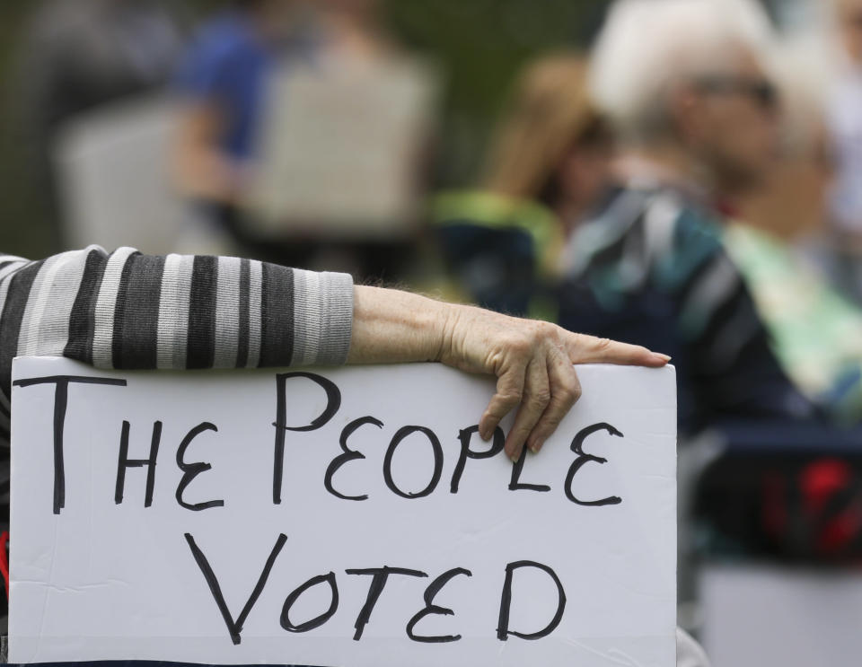 A rally attendee props up a sign with her hand while listening to speakers at the Tuesday, April 27, 2021, Medicaid expansion rally at the Missouri State Capitol in Jefferson City. The Missouri Legislature is the latest statehouse fighting to undo voter-backed ballot measures. Missouri's GOP-led Senate this week voted against paying for voter-approved Medicaid expansion. (Liv Paggiarino/The Jefferson City News-Tribune via AP)
