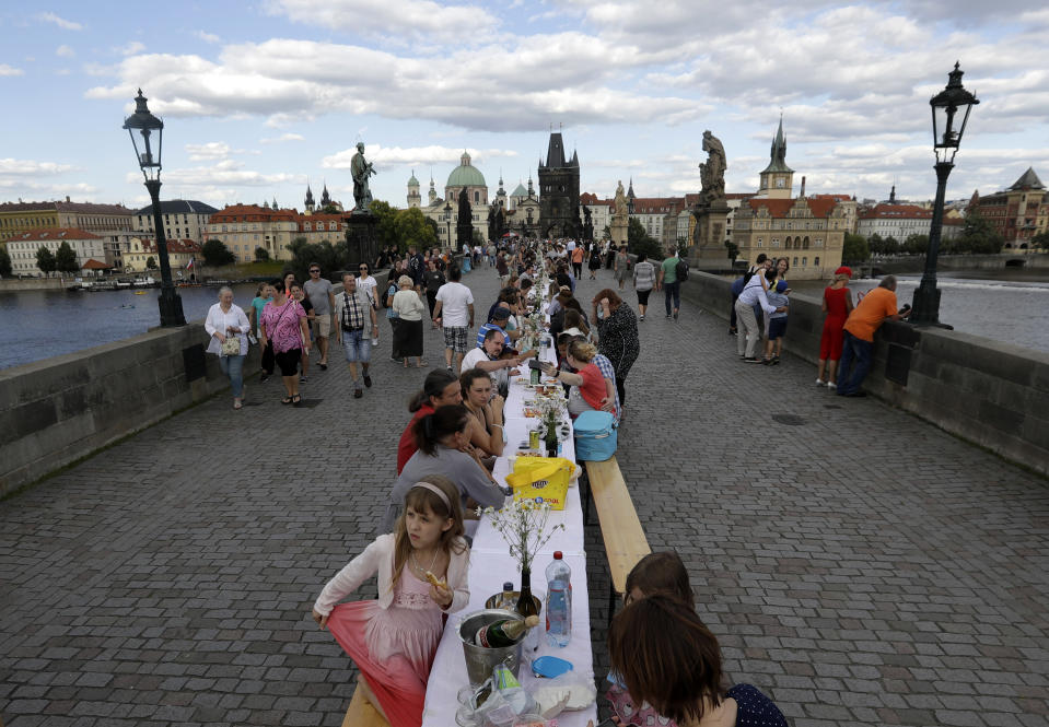 FILE - In this Tuesday, June 30, 2020 file photo, residents sit to dine on a 500 meter long table set on the medieval Charles Bridge, after restrictions were eased following the coronavirus pandemic in Prague, Czech Republic. Czechs had been assured it wouldn't happen again. But amid a record surge of coronavirus infections that's threatening the entire health system with collapse, the Czech Republic is adopting on Thursday exactly the same massive restrictions it slapped on citizens in the spring. (AP Photo/Petr David Josek, File)