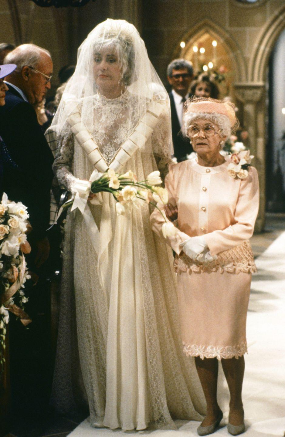 <p>When Dorothy leaves her roommates to marry Stan, the bride chose an old-fashioned look. Set with a lace illusion neck and high collar, Dorothy's dress featured panels of fabric that ran from her shoulders to her waist. Naturally, Sophia was by her side wearing a pale pink suit and pillbox cap. </p>