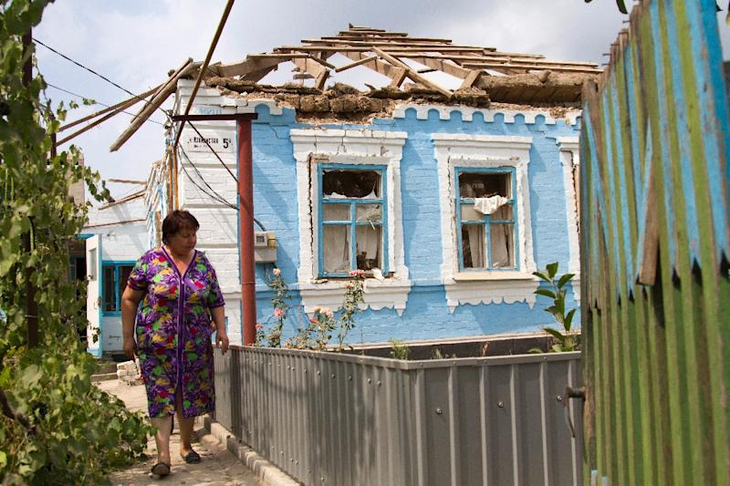 A resident walks in front of her house destroyed by shelling perpetrated by pro-Russian separatists in the village of Sartana, near Mariupol, Donetsk region, on August 17, 2015