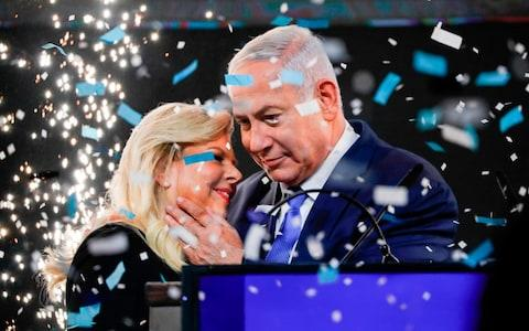 Israeli Prime Minister Benjamin Netanyahu embraces his wife Sara as confetti and fireworks are blown during his appearance before supporters at his Likud Party headquarters in the Israeli coastal city of Tel Aviv on election night early on April 10, 2019.  - Credit: AFP