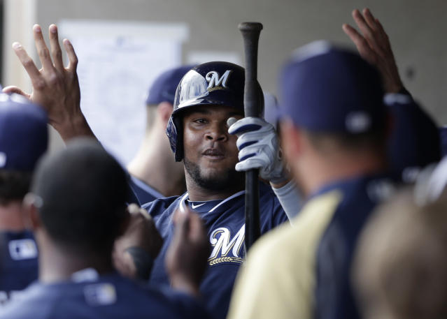 Milwaukee Brewers' Juan Francisco is greeted in the dugout after hitting his second home run against the Oakland Athletics during the fourth inning of a spring training baseball game on Thursday, Feb. 27, 2014, in Scottsdale, Ariz. (AP Photo/Gregory Bull)