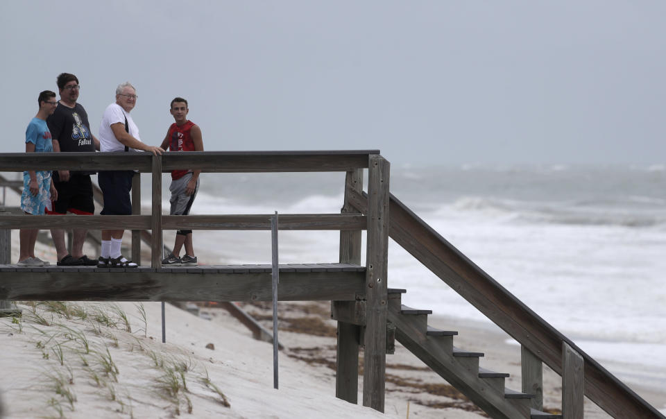 Beach goers watch waves churned up by Tropical Storm Isaias near Jaycee Beach Park, Sunday, Aug. 2, 2020, in Vero Beach, Fla. Isaias weakened from a hurricane to a tropical storm late Saturday afternoon, but was still expected to bring heavy rain and flooding as it barrels toward Florida. (AP Photo/Wilfredo Lee)
