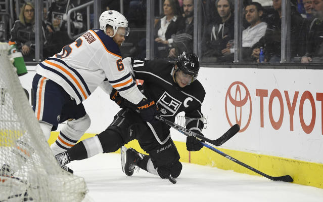 Los Angeles Kings center Anze Kopitar, of Slovenia, falls as he and Edmonton Oilers defenseman Adam Larsson, of Sweden, go after the puck during the second period of an NHL hockey game Saturday, Feb. 24, 2018, in Los Angeles. (AP Photo/Mark J. Terrill)