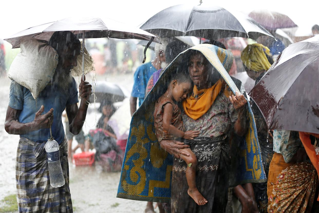Rohingya refugees stands in an open place during heavy rain, as they are held by Border Guard Bangladesh after illegally crossing the border, in Teknaf, Bangladesh, on Aug. 31, 2017.