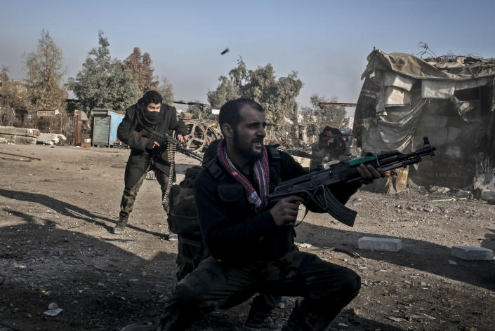 Free Syrian Army fighters fire their weapons during heavy clashes with government forces in Aleppo, Syria, Sunday, Jan. 20, 2013. The revolt against President Bashar Assad began in March 2011with peaceful protests but morphed into a civil war that has killed more than 60,000 people, according to a recent United Nations recent estimate. (AP Photo/Andoni Lubaki)