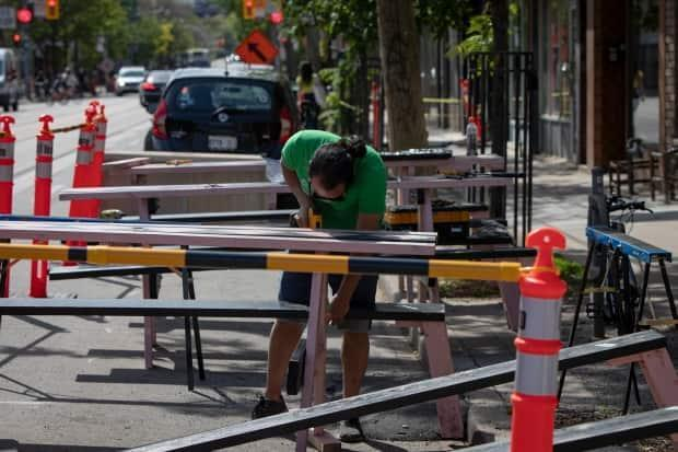 Christian Cruz assembles picnic tables outside the Black Dice Cafe in Toronto. As part of Phase 1 of Ontario's reopening plan, people can dine with up to four others on patios. (Evan Mitsui/CBC - image credit)
