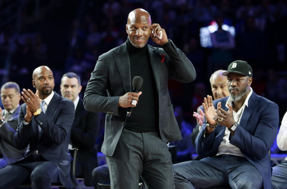 Former Detroit Piston Chauncey Billups, center, addresses fans at Little Caesars Arena while Richard Hamilton, left, and Ben Wallace look on during a celebration of their 2004 NBA Championship during halftime of an NBA basketball game against the Charlotte Hornets, Sunday, April 7, 2019, in Detroit. (AP Photo/Duane Burleson)