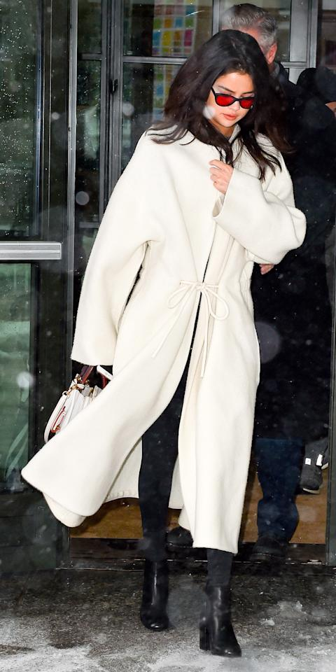 <p>Gomez braved the New York City snow in a chic winter white coat that featured a delicate bow accent at the waist. She paired the topper with a contrasting pair of black skinny pants and matching boots, and finished her ensemble with a white leather bag and red sunnies.</p>