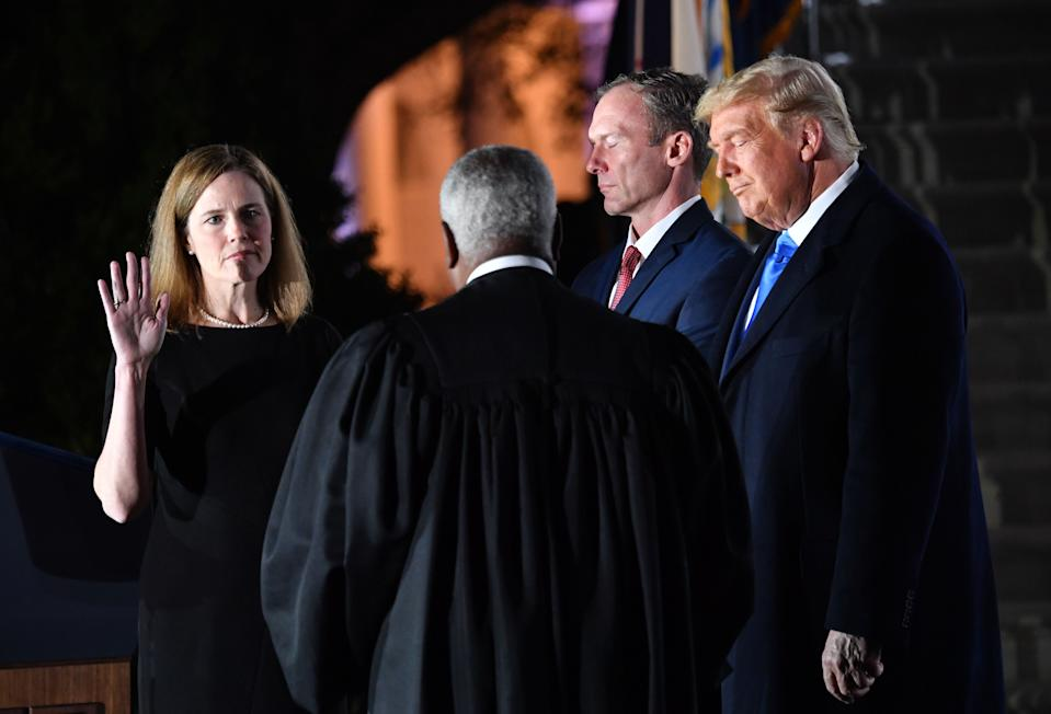 US President Donald Trump watches as Supreme Court Associate Justice Clarence Thomas swears in Amy Coney Barrett as a US Supreme Court Associate Justice, flanked by her husband Jesse M. Barrett, during a ceremony on the South Lawn of the White House October 26, 2020, in Washington, DC.