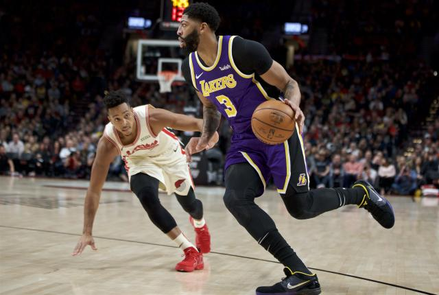 Los Angeles Lakers forward Anthony Davis, right, dribbles past Portland Trail Blazers guard CJ McCollum during the first half of an NBA basketball game in Portland, Ore., Friday, Dec. 6, 2019. (AP Photo/Craig Mitchelldyer)