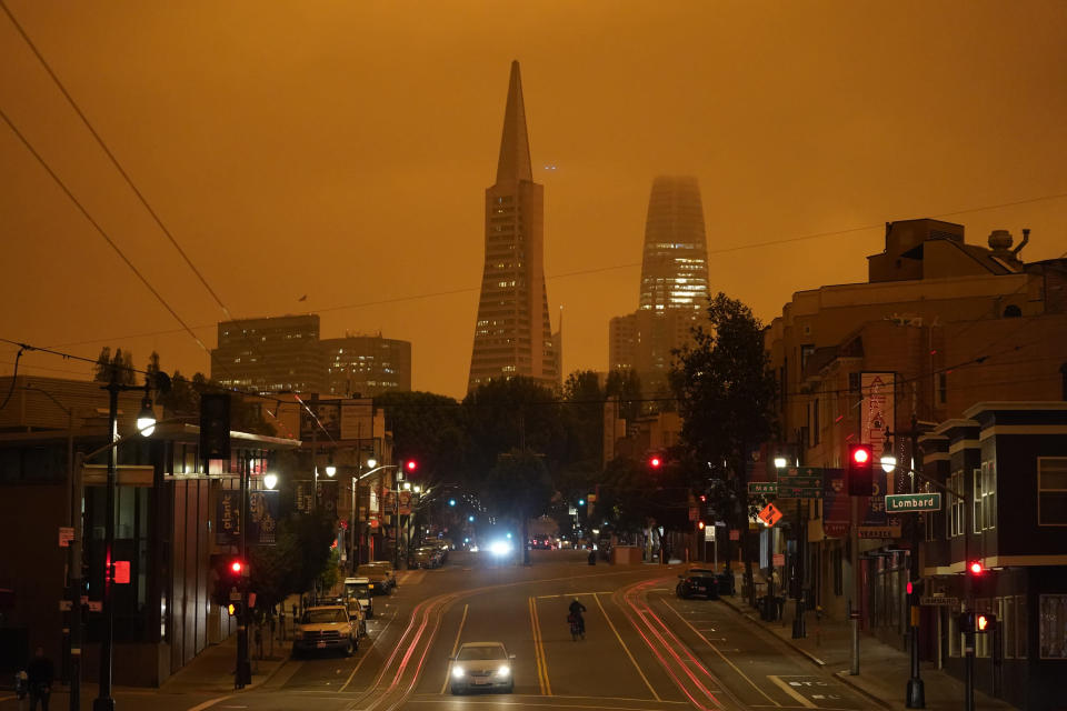 FILE - In this Sept. 9, 2020, file photo, taken at 11:42 a.m., an orange sky is seen over Columbus Ave., the Transamerica Pyramid and Salesforce Tower caused by heavy smoke from wildfires in San Francisco. Wildfires that scorched huge swaths of the West Coast churned out massive plumes of choking smoke that blanketed millions of people with hazardous pollution that spiked emergency room visits and that experts say could continue generating health problems for years. An Associated Press analysis of air quality data shows 5.2 million people in five states were hit with hazardous levels of pollution for at least a day. (AP Photo/Eric Risberg, File)