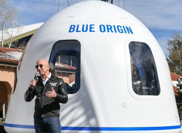 Amazon billionaire Jeff Bezos takes questions in front of Blue Origin's mock-up for the New Shepard spaceship's crew capsule. (GeekWire Photo / Kevin Lisota)