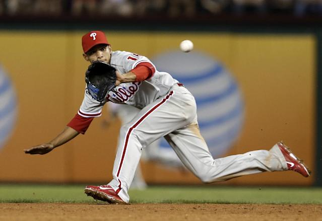 Philadelphia Phillies second baseman Cesar Hernandez chases down grounder by Texas Rangers' Alex Rios, who was out at first in the third inning of a baseball game, Tuesday, April 1, 2014, in Arlington, Texas. (AP Photo/Tony Gutierrez)