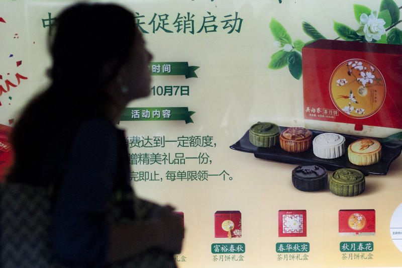 In this Wednesday, Sept. 11, 2013 photo, a commuter walks past a mooncake advertisement in a subway station in Beijing, China. The mooncake, a traditional Chinese pastry given as a gift during the Chinese mid-autumn festival, has become the unlikely latest casualty of Beijing's anti-corruption campaign. (AP Photo/Alexander F. Yuan)