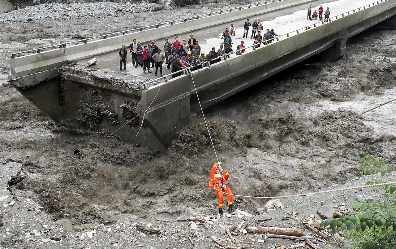 WENCHUAN, CHINA - JULY 04: (CHINA OUT) A firefighter uses a rope slide as he rescues trapped people from a damaged bridge of Yingxiu town on July 4, 2011  in Wenchuan, Sichuan Province of China. Some sections of the state highway 213 were destroyed by mudslide after a heavy rain hit Wenchuan county region on Monday. (Photo by ChinaFotoPress/Getty Images)