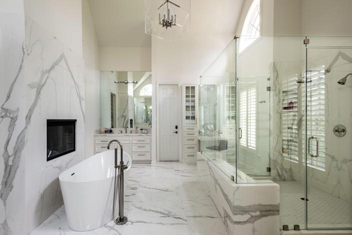 The pitched ceiling washes the bathroom in gorgeous southern light, which bounces off the white Neolith sintered stone seen on nearly every surface. A pass-through fireplace adds a spa-like touch. All the fixtures are polished nickel; the acrylic light fixture was custom-designed by Loya.