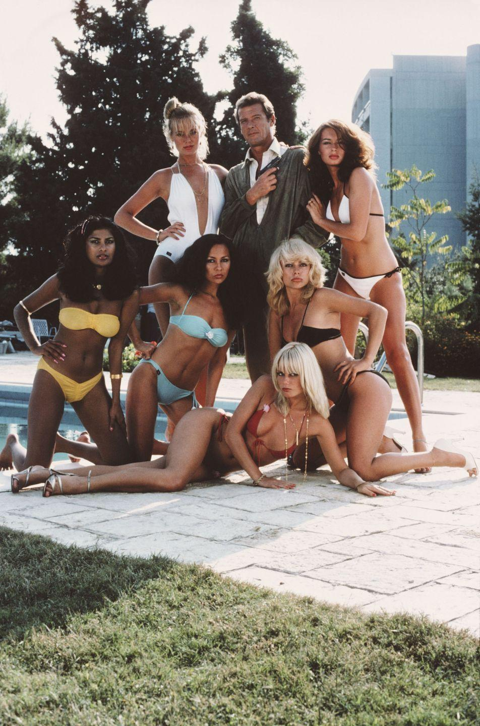 <p>Roger Moore as 007, surrounded by bikini-clad women in a publicity still for For Your Eyes Only.</p>
