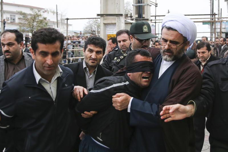 This picture provided by ISNA, a semi-official news agency, taken on Tuesday, April 15, 2014 shows Iranian officials and security escorting away the blindfolded man Bilal from the scene of his execution in public in the northern city of Nour, Iran. Bilal, who was convicted of killing Abdollah Hosseinzadeh, was pardoned by the victim's family moments before being executed. (AP Photo/ISNA, Arash Khamoushi)