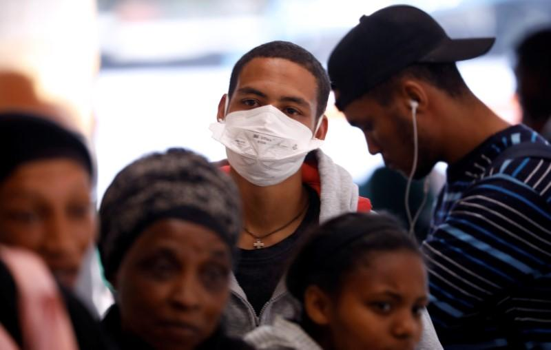 A commuter wears a mask  to combat the spread of coronavirus disease (COVID-19) at a bus depot in Cape Town