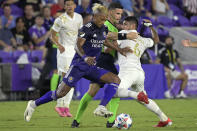 Orlando City forward Nani, front, takes the ball as Atlanta United defender Alan Franco (6) is blocked by an official during the first half of an MLS soccer match Friday, July 30, 2021, in Orlando, Fla. (Phelan M. Ebenhack/Orlando Sentinel via AP)