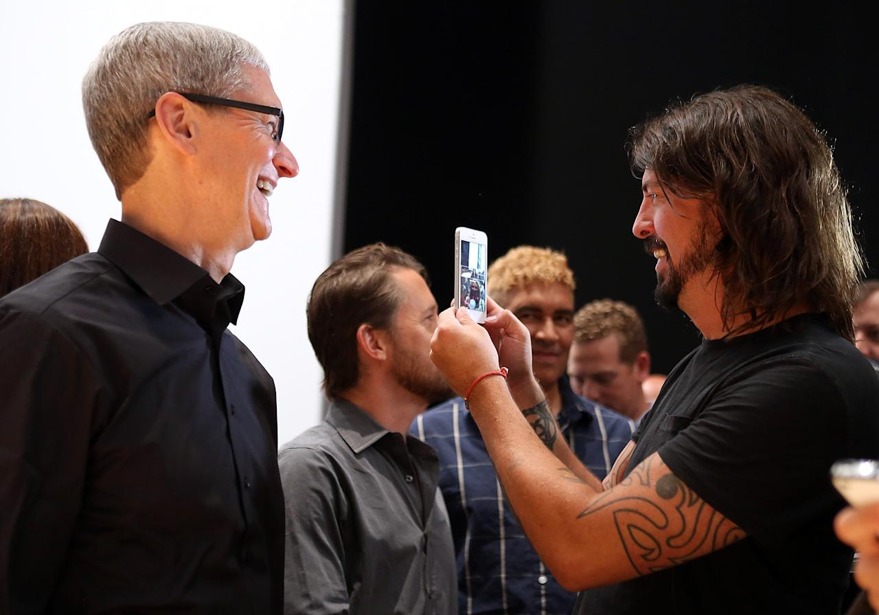 SAN FRANCISCO, CA - SEPTEMBER 12:  Apple CEO Tim Cook (L) looks on as Dave Grohl of the Foo Fighters looks at the new iPhone 5 during an Apple special event at the Yerba Buena Center for the Arts on September 12, 2012 in San Francisco, California. Apple announced the iPhone 5, the latest version of the popular smart phone.  (Photo by Justin Sullivan/Getty Images)