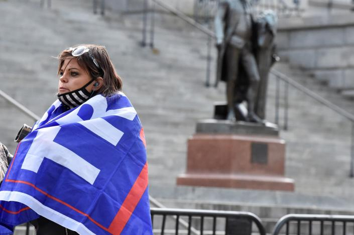 A woman with a Trump flag draped around her shoulders stands near a blocked off statue of George Washington at South Carolina's Statehouse on Sunday, Jan. 17, 2021, in Columbia, S.C. Law enforcement has been stepped up at state capitols across the country during an expected week of unrest surrounding President-elect Joe Biden's inauguration. (AP Photo/Meg Kinnard)