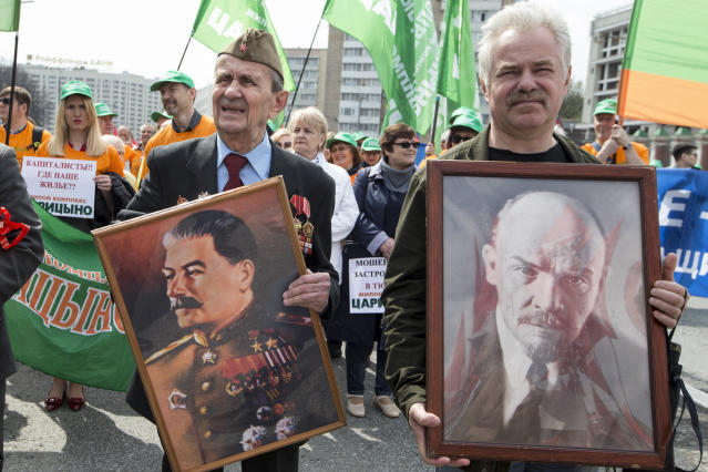 <p>Two elderly men carry portraits of Soviet founder Vladimir Lenin, right, and former Soviet leader Josef Stalin during a Communist rally to mark May Day in Moscow, Russia, May 1, 2018. Workers and activists marked May Day on Tuesday with rallies to demand their government address labor issues. (Photo: Alexander Zemlianichenko/AP) </p>