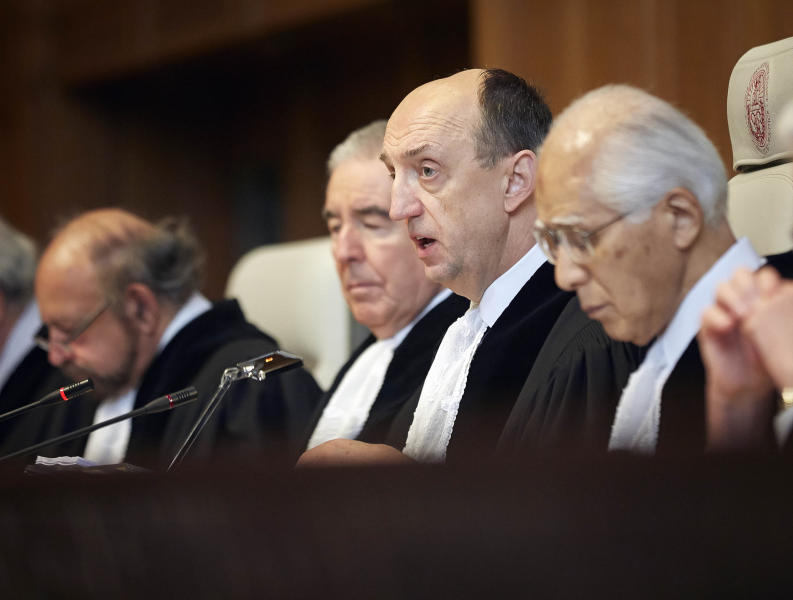 Judge Peter Tomka, center, president of the International Court of Justice, delivers its verdict in The Hague, Netherlands, Monday March 31, 2014. The International Court of Justice is ruling Monday on Australia's challenge against Japan for whaling in Antarctic waters. (AP Photo/Phil Nijhuis)